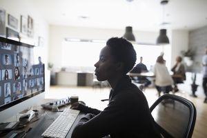 A woman browsing photos on a computer.