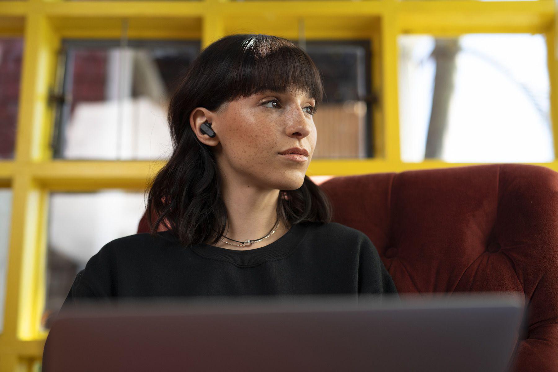 Woman wearing Skullcandy Dime earbuds