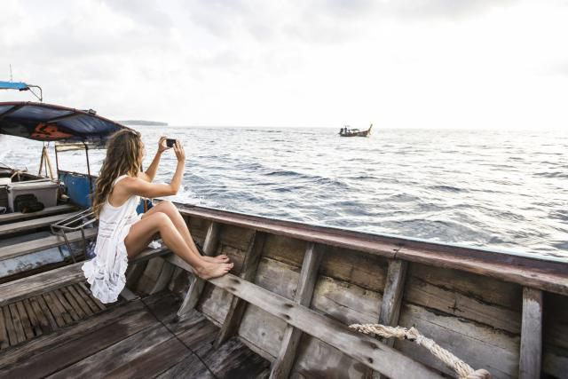 Girl taking a photo on a boat