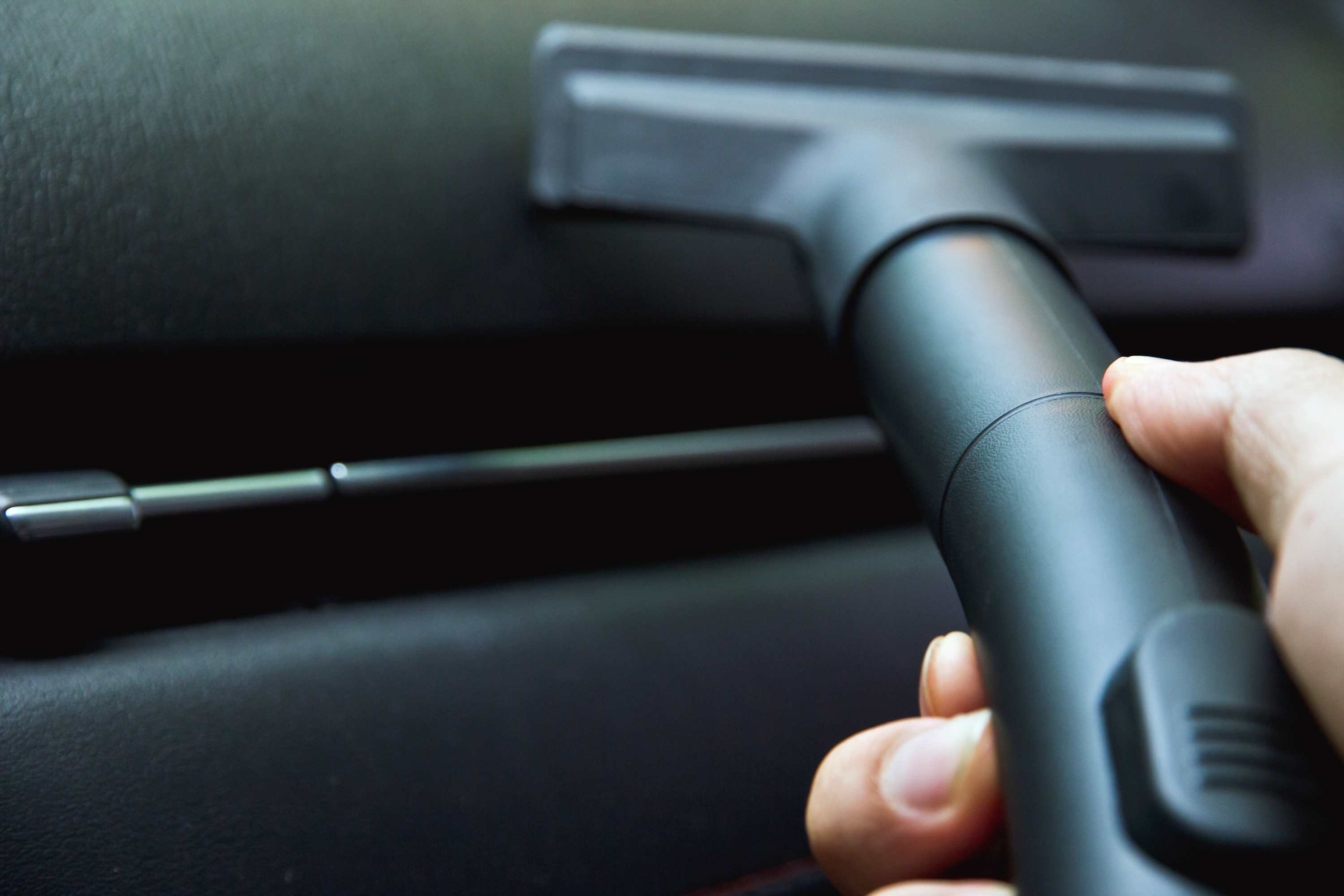 Hand cleaning car with vacuum cleaner