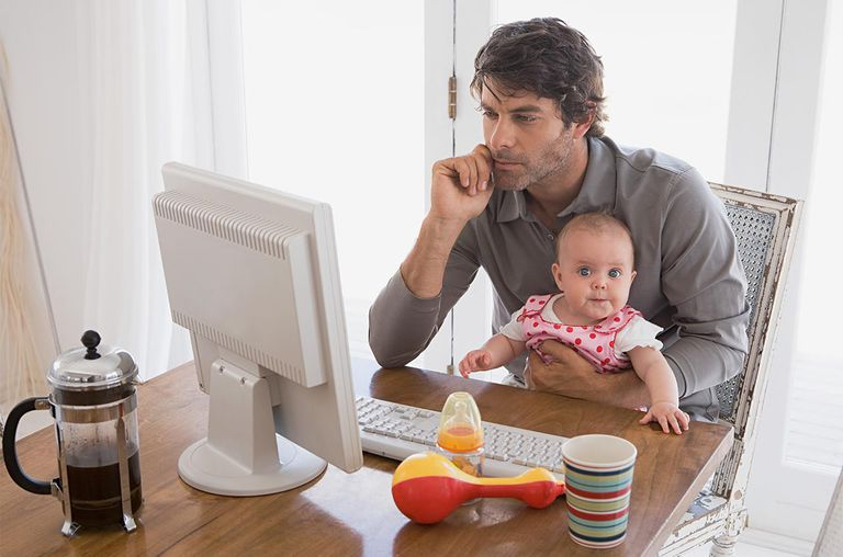 A man holding his baby and looking at a computer