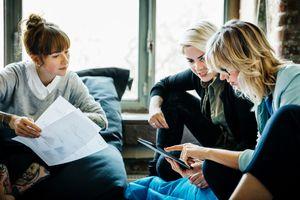Three business women going over a digital document.