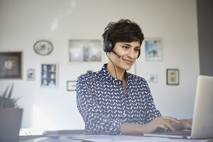 A woman smiling at a laptop with a headset on her head