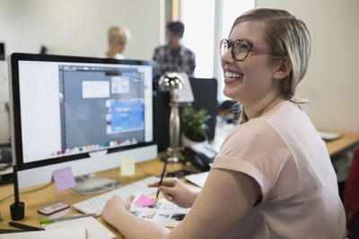 Smiling graphic designer working at computer in office