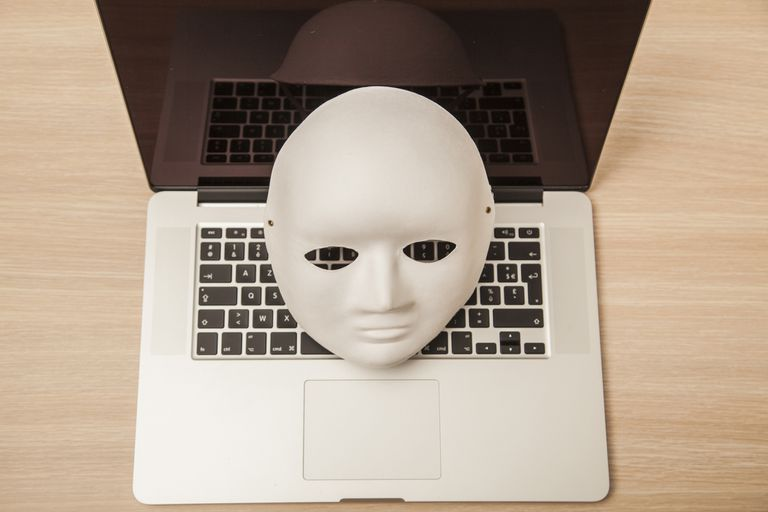 A mask sitting on a laptop.