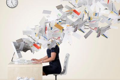 Businesswoman's head covered with paperwork flying out of her computer screen