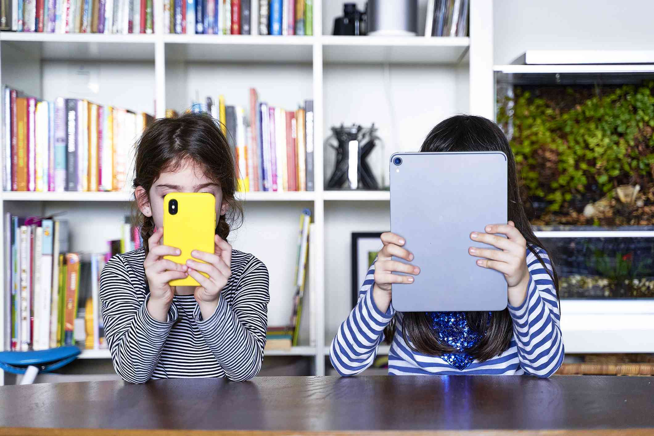 Two sisters sitting side by side at table in the living room using electronic devices