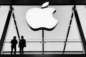 Two people looking through a window with the Apple logo above them.