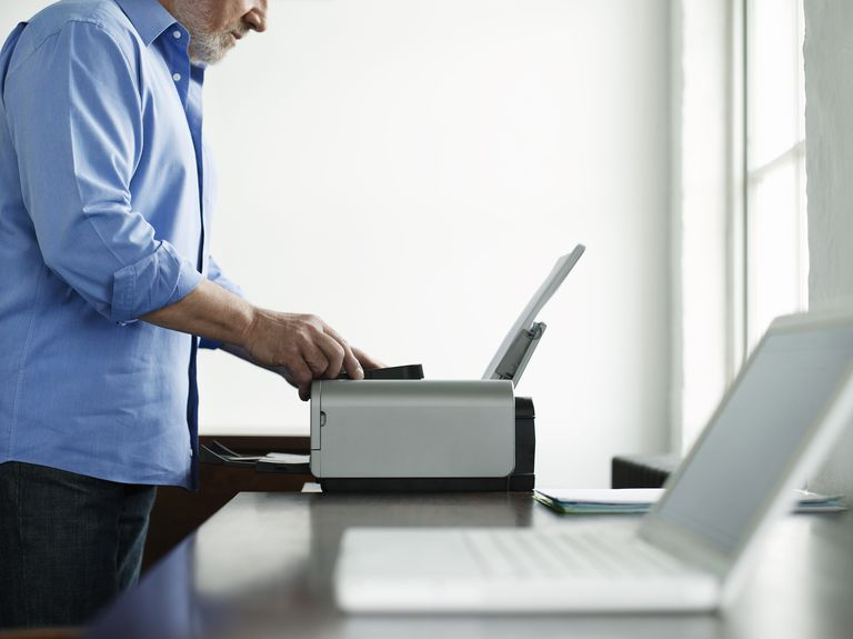 A man using a printer on a desk.