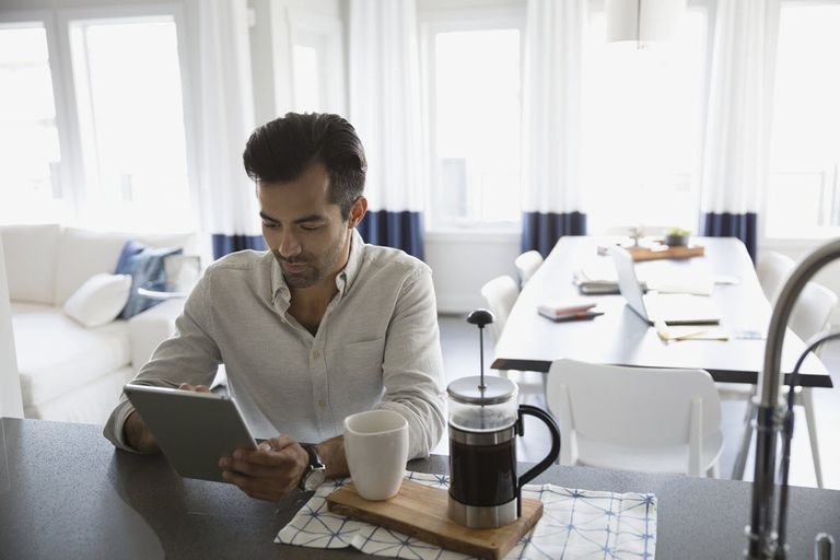Man with a concentrated look using a tablet at a countertop with coffee.