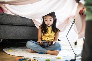 A young girl sitting on a rug next to a couch under a sheet looking at a tablet during the day