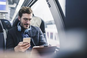 Man on train with headphones, phone, and laptop