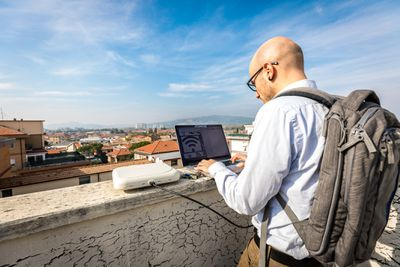 A traveler with a backpack using Wi-Fi on a laptop