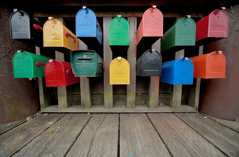 Various colored mailboxes in wooden structure