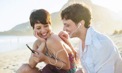Man and woman sharing music at beach with AUX cables and ear buds