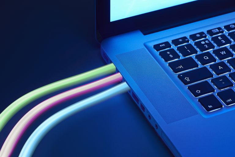Fibre optic broadband represented by blue, green, and red lights coming out of macbook laptop