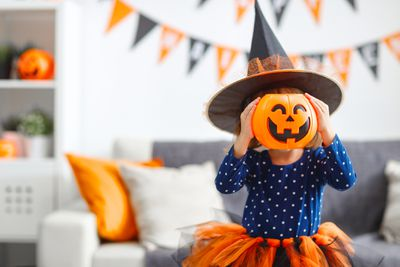 A young girl wearing an orange skirt, blue top, and witch's hat, holds a pumpkin in front of her face