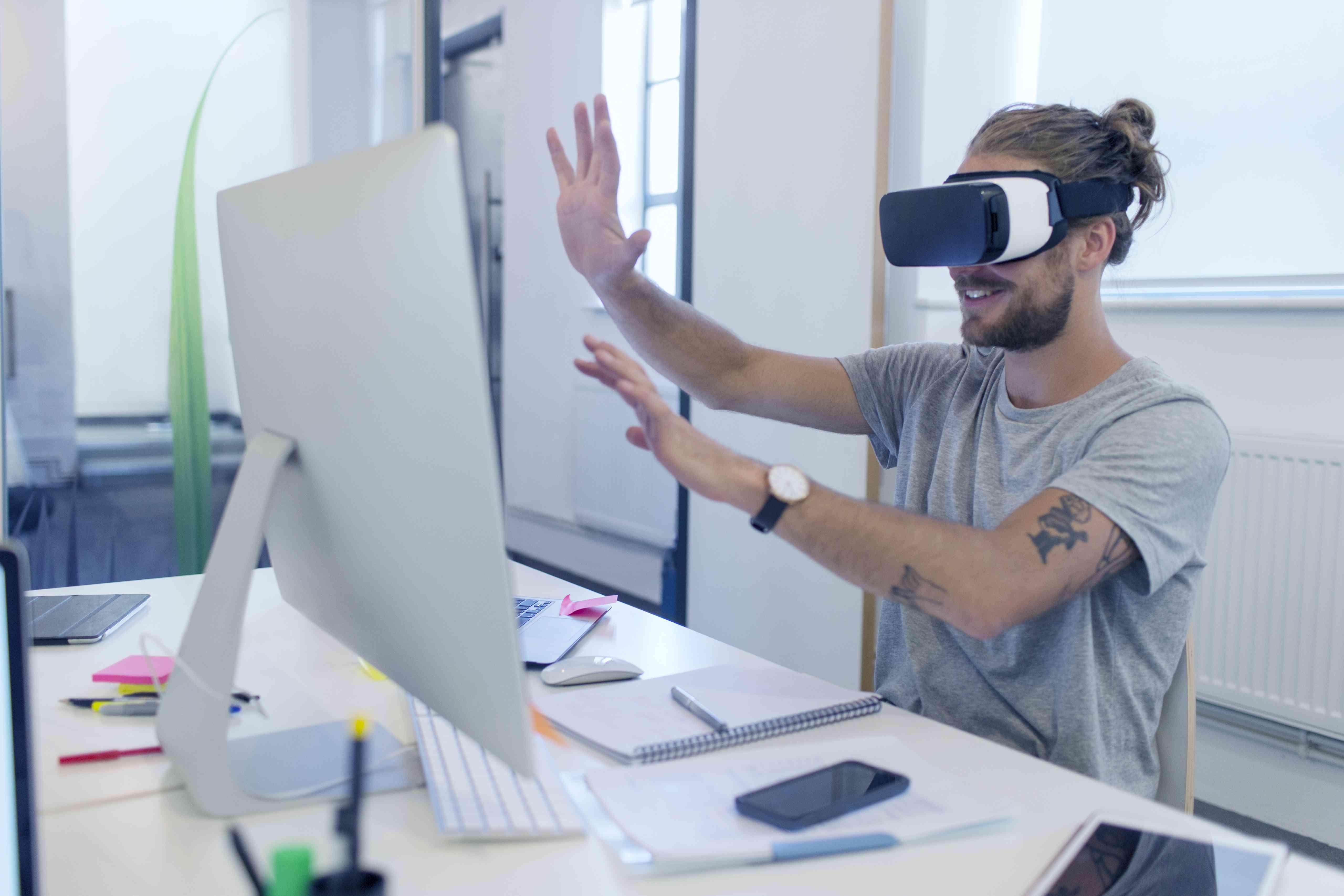 Computer programmer programming virtual reality simulator glasses at computer in office