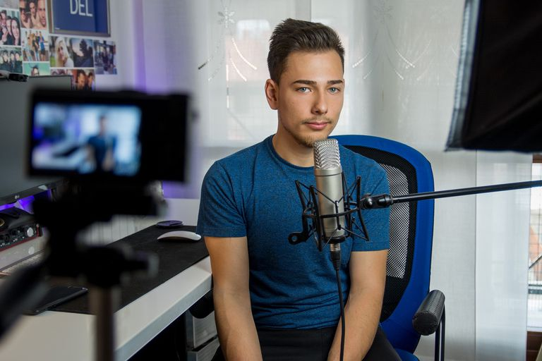 A stock photo of a young man recording a video from home, ostensibly to be posted on a video sharing website like YouTube.