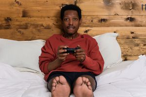 A man sitting on a bed holding a games controller