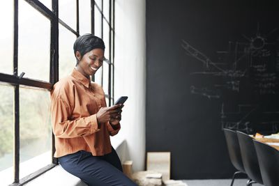 A woman leaning on a window sill smiling at her smartphone