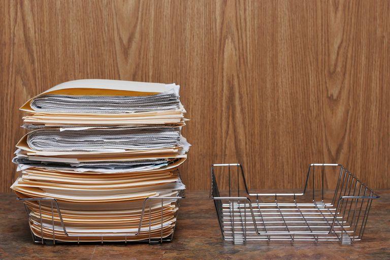 Pile of folders in wire basket next to empty basket