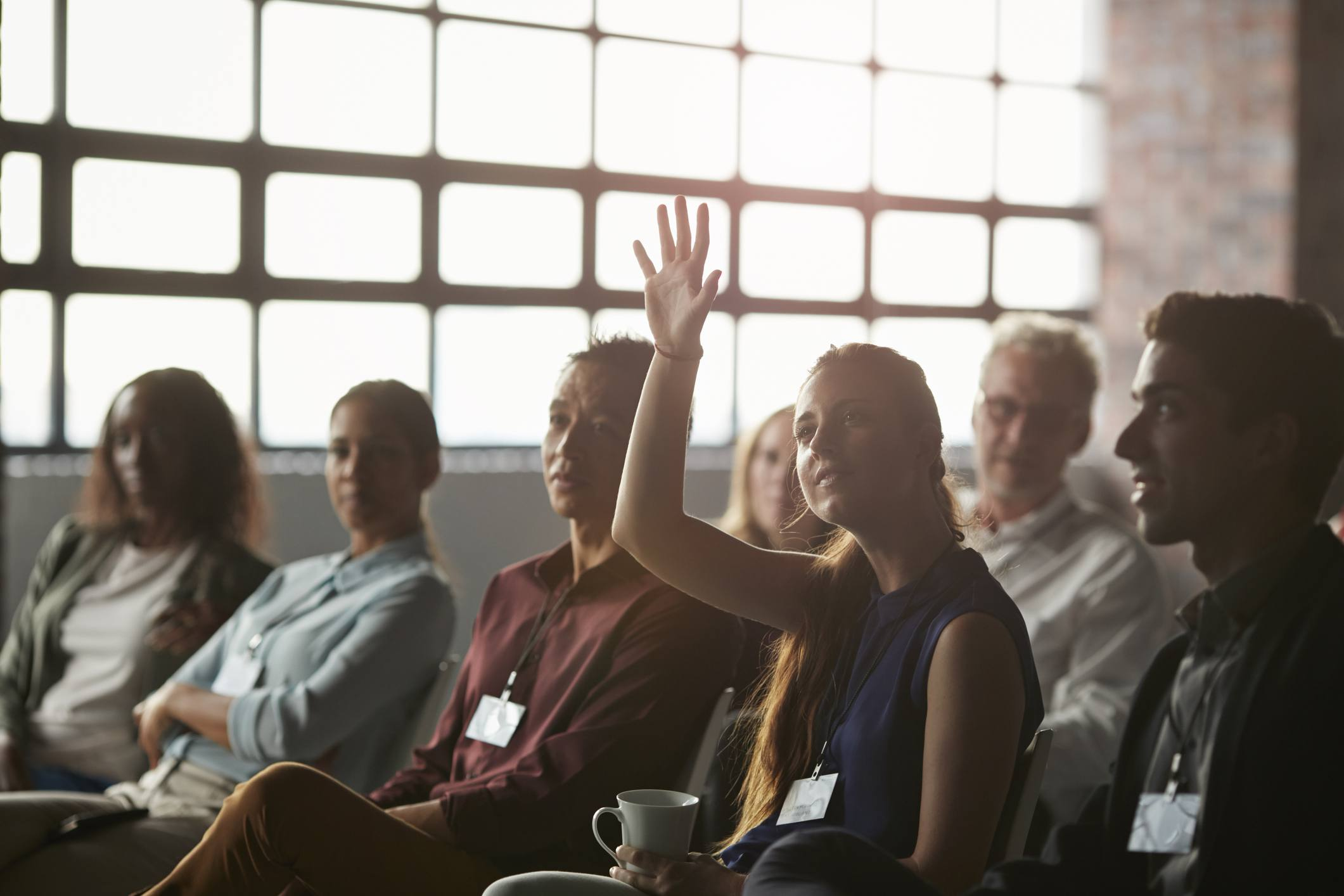 Woman raising hand in group of people sitting for presentation