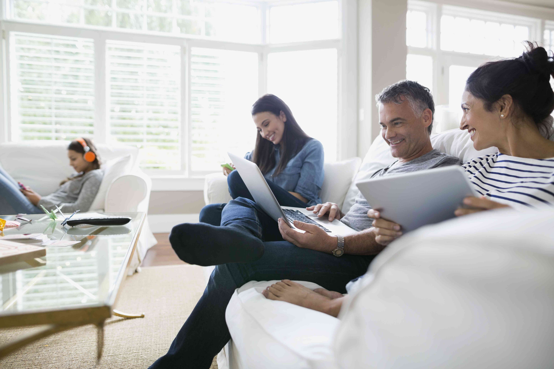 Family using wireless technology on living room sofa