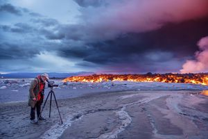Photographer filming the volcano eruption at the Holuhraun Fissure, near the Bardarbunga Volcano, Ic