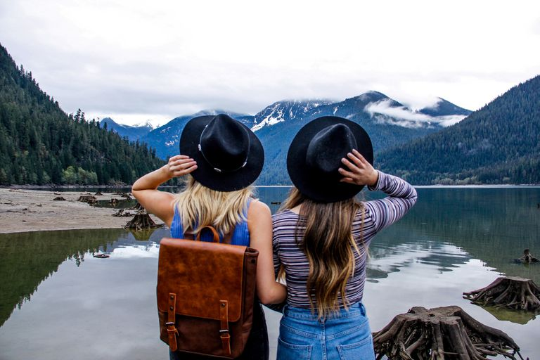 A pair of friends looking at a lake and mountains.