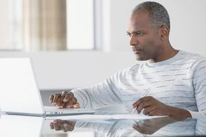 Middel-aged man muting browser tabs on his laptop computer.