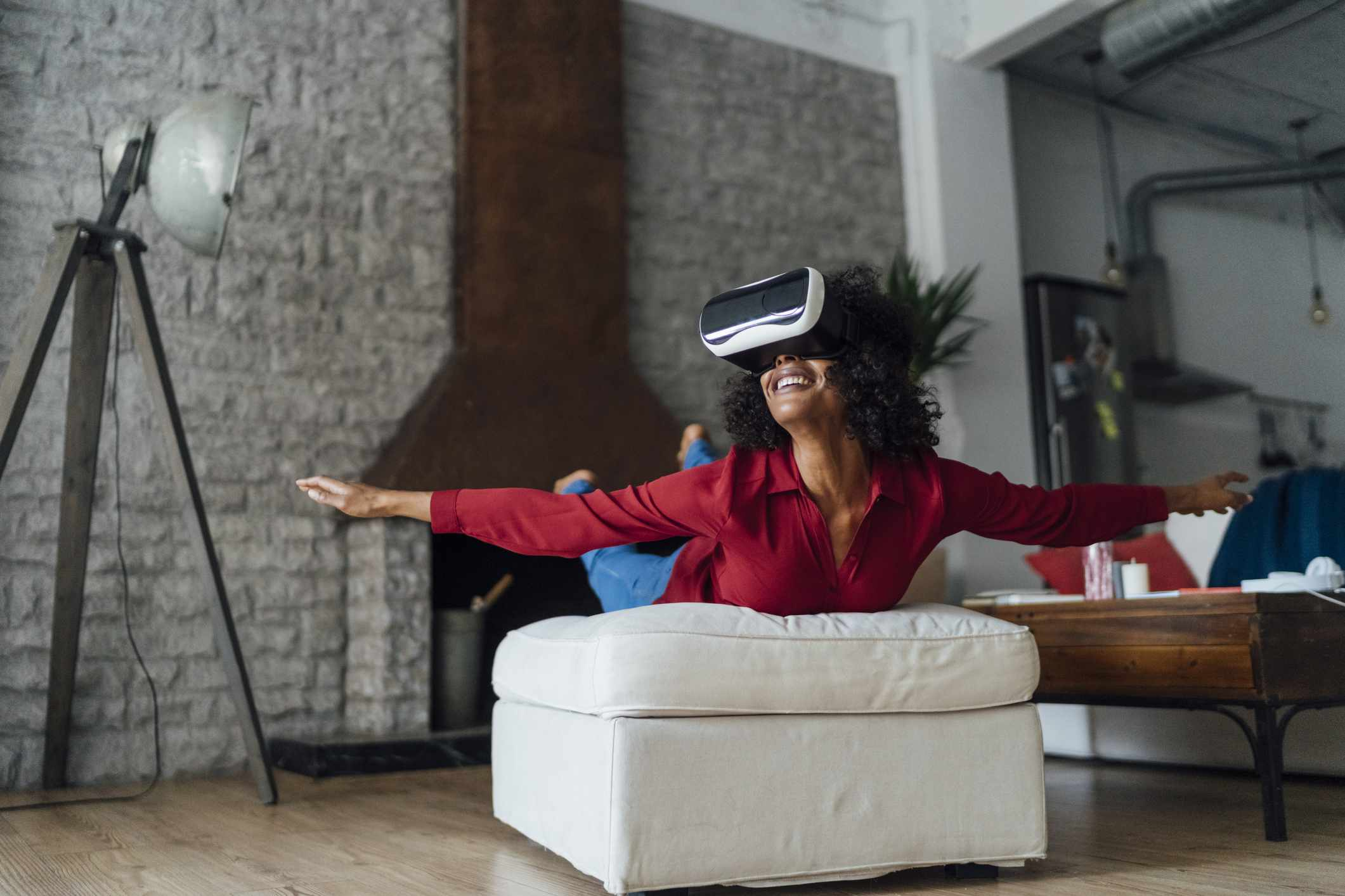 Woman lying on seating furniture, wearing VR goggles, pretending to fly