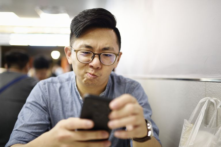 Male in glasses holding phone with an annoyed expression