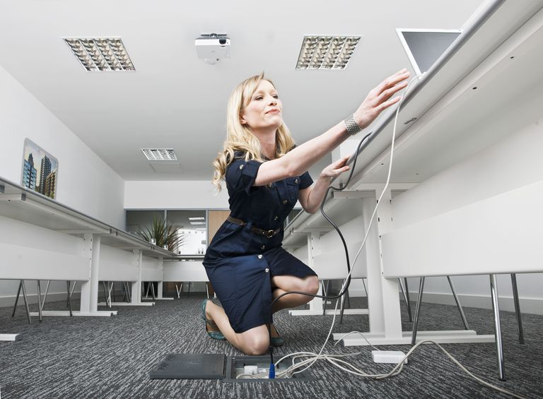 Woman kneeling on ground while arranging power and data cables in an office.