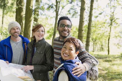 Four travelers holding map and smiling in park.