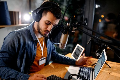 A man recording a podcast with a microphone and laptop.