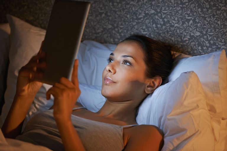Woman looking at a tablet in bed