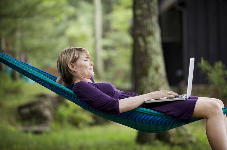 Woman laying on a hammock with a computer