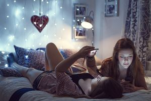 Two young women on a bed with iPhones and lights, depicting using Siri to control home lights