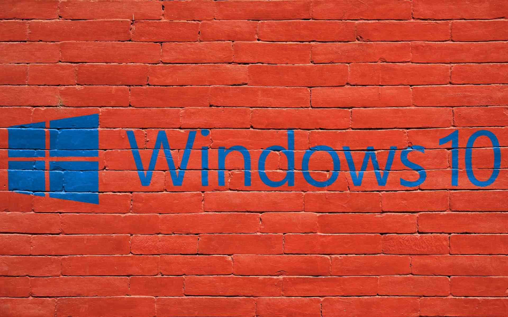 Windows 10 logo painted on a red brick wall.