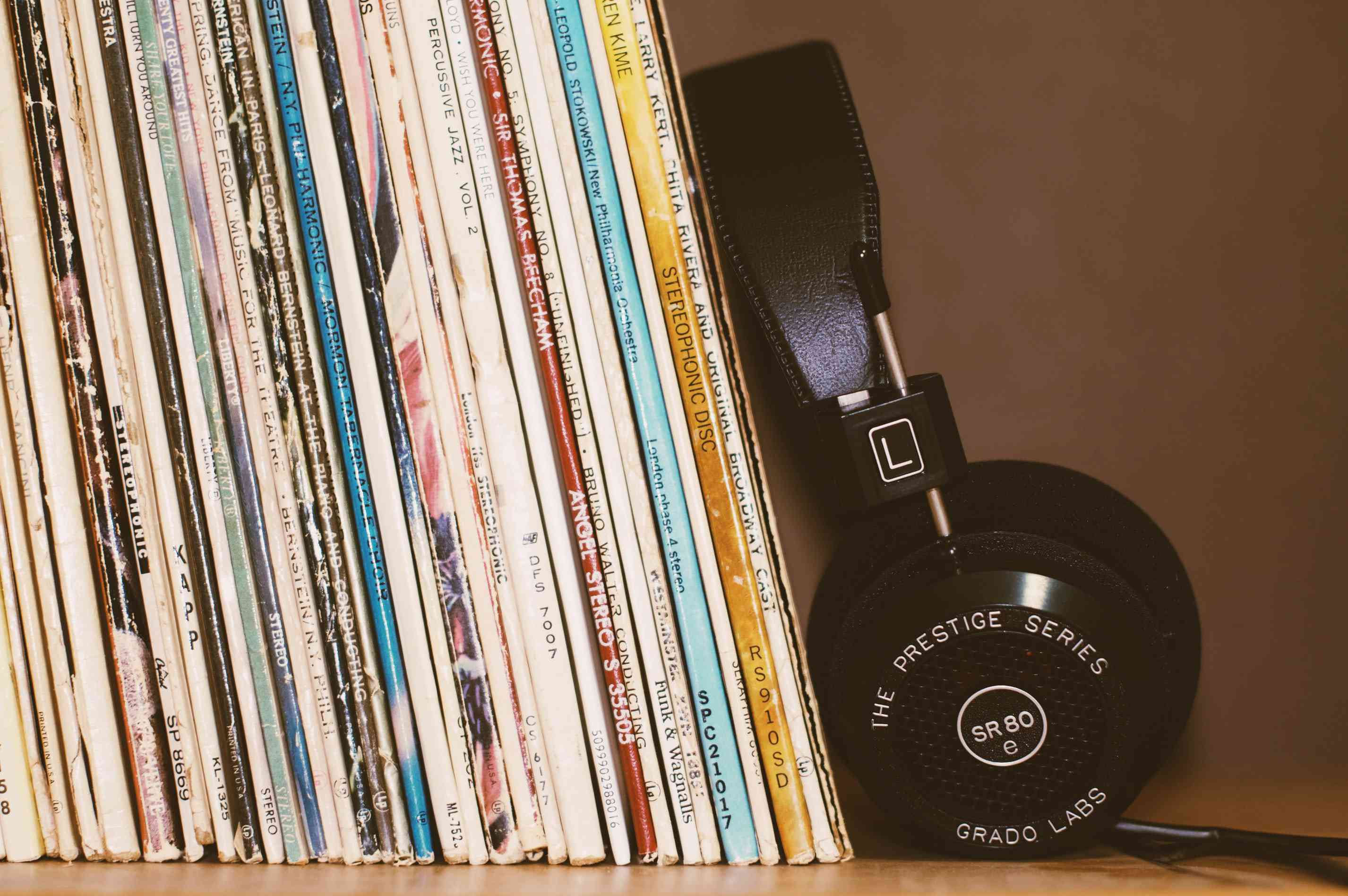 wireless headphones leaning against books