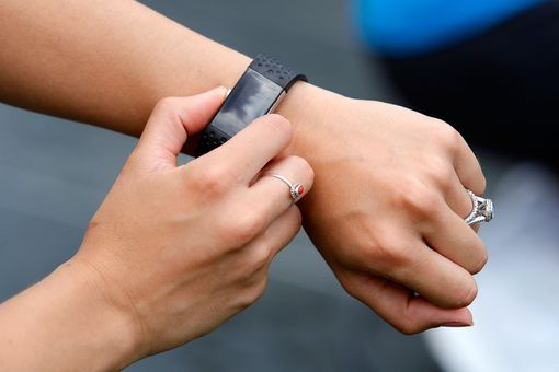 Photograph of a woman checking her stats on the Fitbit Charge 2