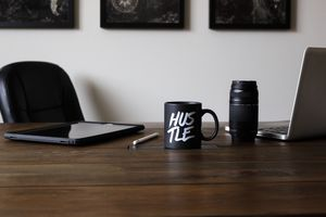 Desk with laptop, tablet, camera and coffee cup