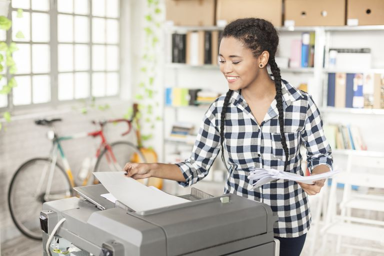 Young female using copy machine at workplace