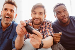 Three men playing Sony's PlayStation video game console