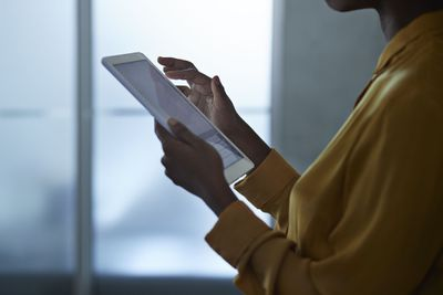 Save to Board Close-up of businesswoman using tablet, at office