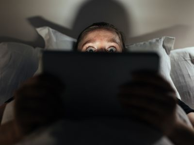 Woman in bed watching a scary movie on her tablet