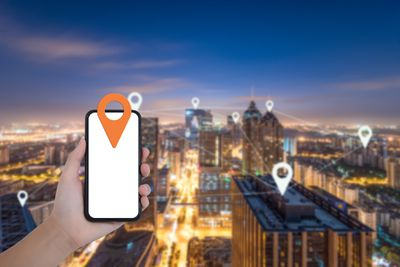 An image of several location pins on different buildings with a hand holding an iPhone with a pin on it