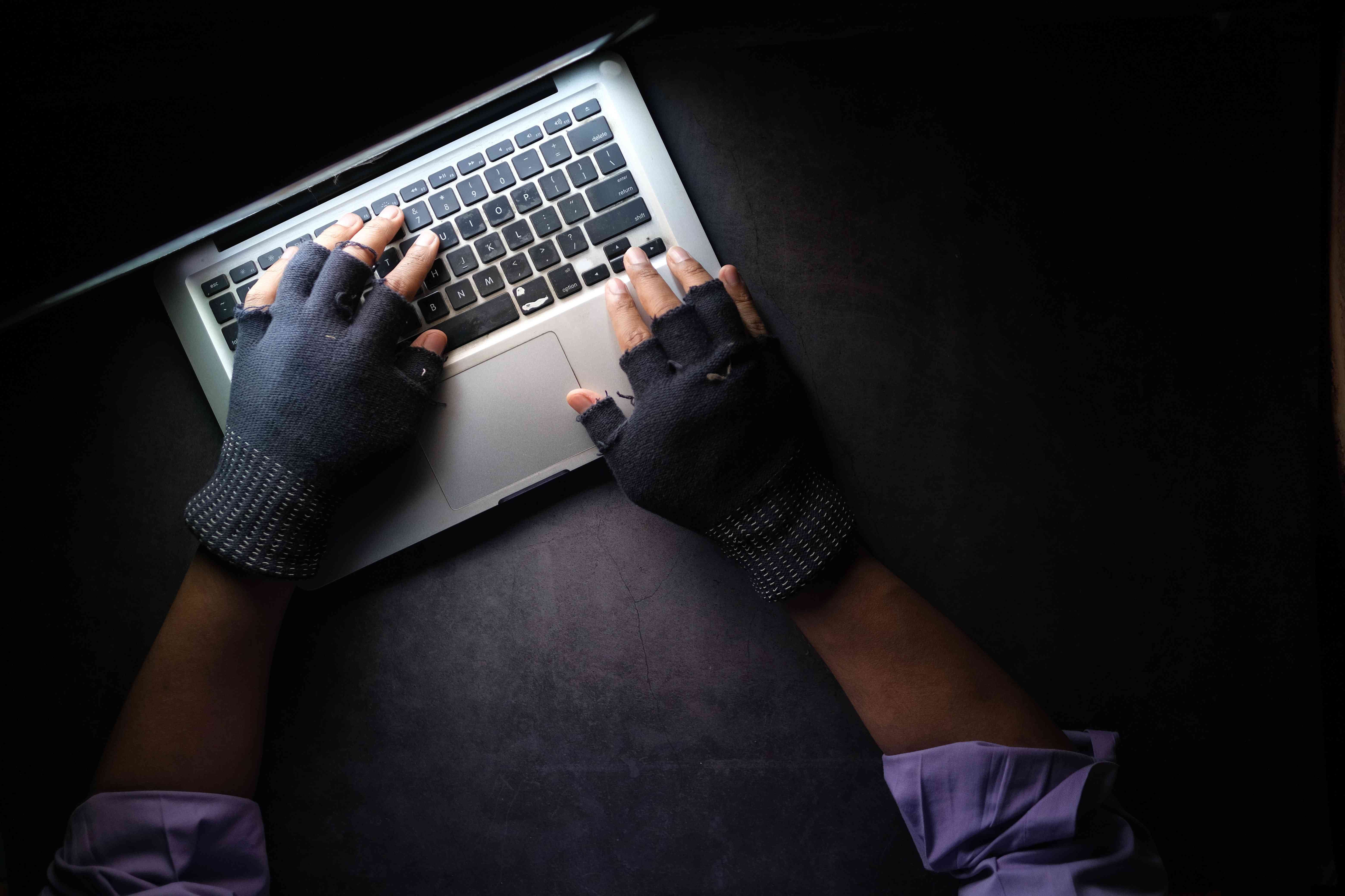View from above of someone with fingerless gloves typing on a laptop to indicate an internet scammer.