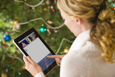 Woman using an iPad in front of a Christmas tree